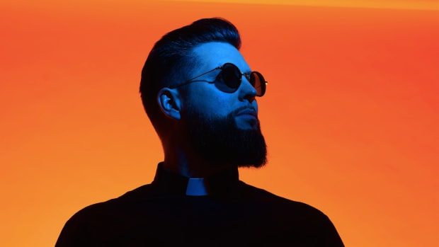 Tchami (real name Martin Bresso) in blue light over an orange background.