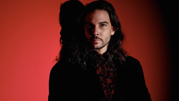 Seven Lions standing against a red background.