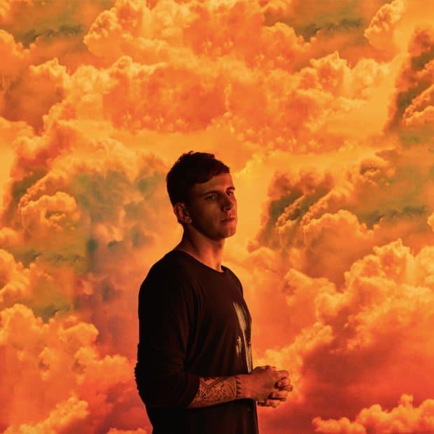 Denver EDM DJ/producer Illenium (real name Nicholas D. Miller) standing in front of orange clouds.