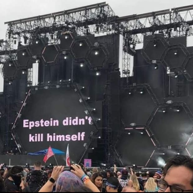 """""""Epstein didn't kill himself"""" displayed on the screen at the end of ATLiens' set at EDC Orlando."""