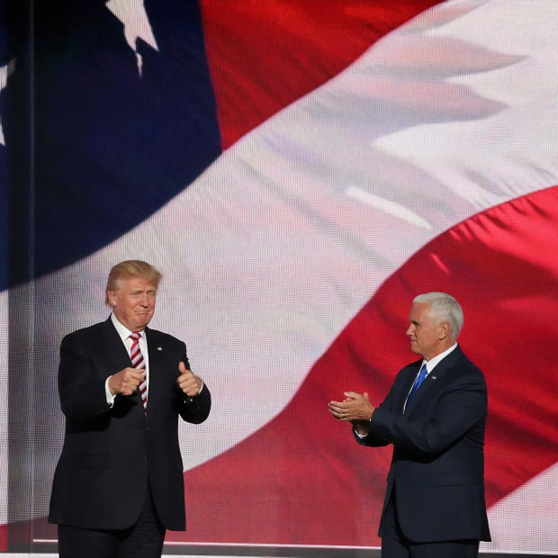 Donald Trump and Mike Pence standing in front of an image of an American flag.