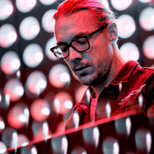 A color photo of DJ/producer Diplo (real name Thomas Wesley Pentz) during a performance.
