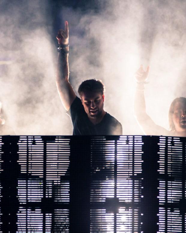 Swedish House Mafia performing with fog around them.