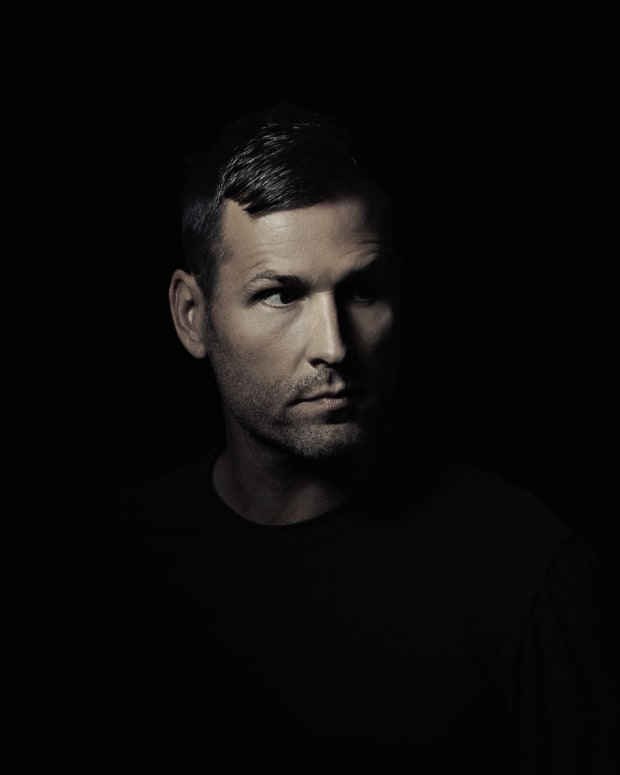 A color headshot of Kaskade (real name Ryan Raddon) over a black background.
