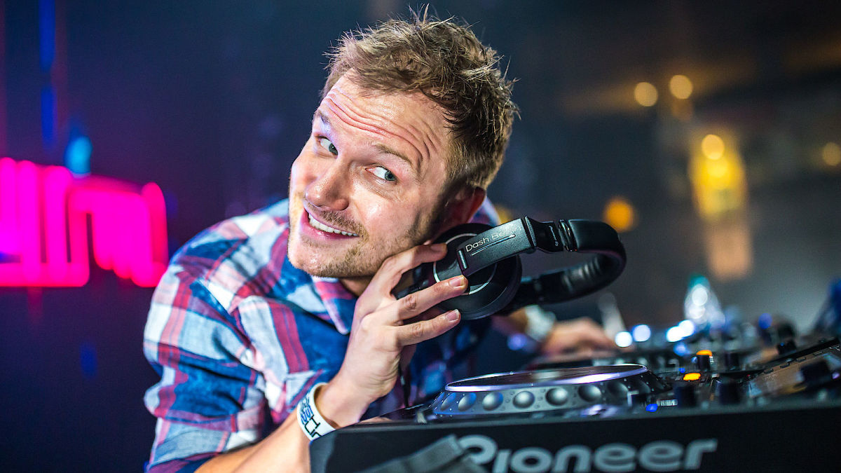 Former Dash Berlin frontman Jeffrey Sutorius playing with a pair of headphones during a DJ performance.