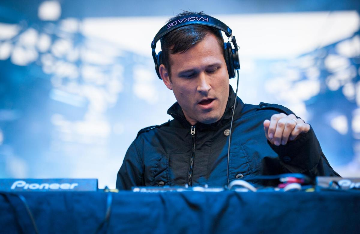 Kaskade during a DJ set with headphones on.