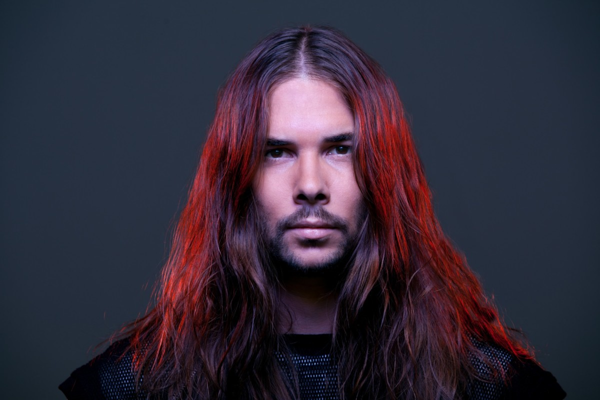 A head shot of DJ/producer Seven Lions A.K.A. Jeff Montalvo with bright red dyed hair.