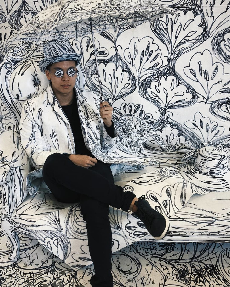 NØLL Wearing Black & White Hat and Jacket That Match Wallpaper Behind Him