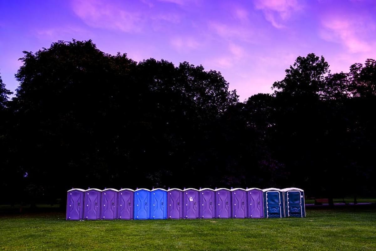 line of port a potties toilets in purple sky
