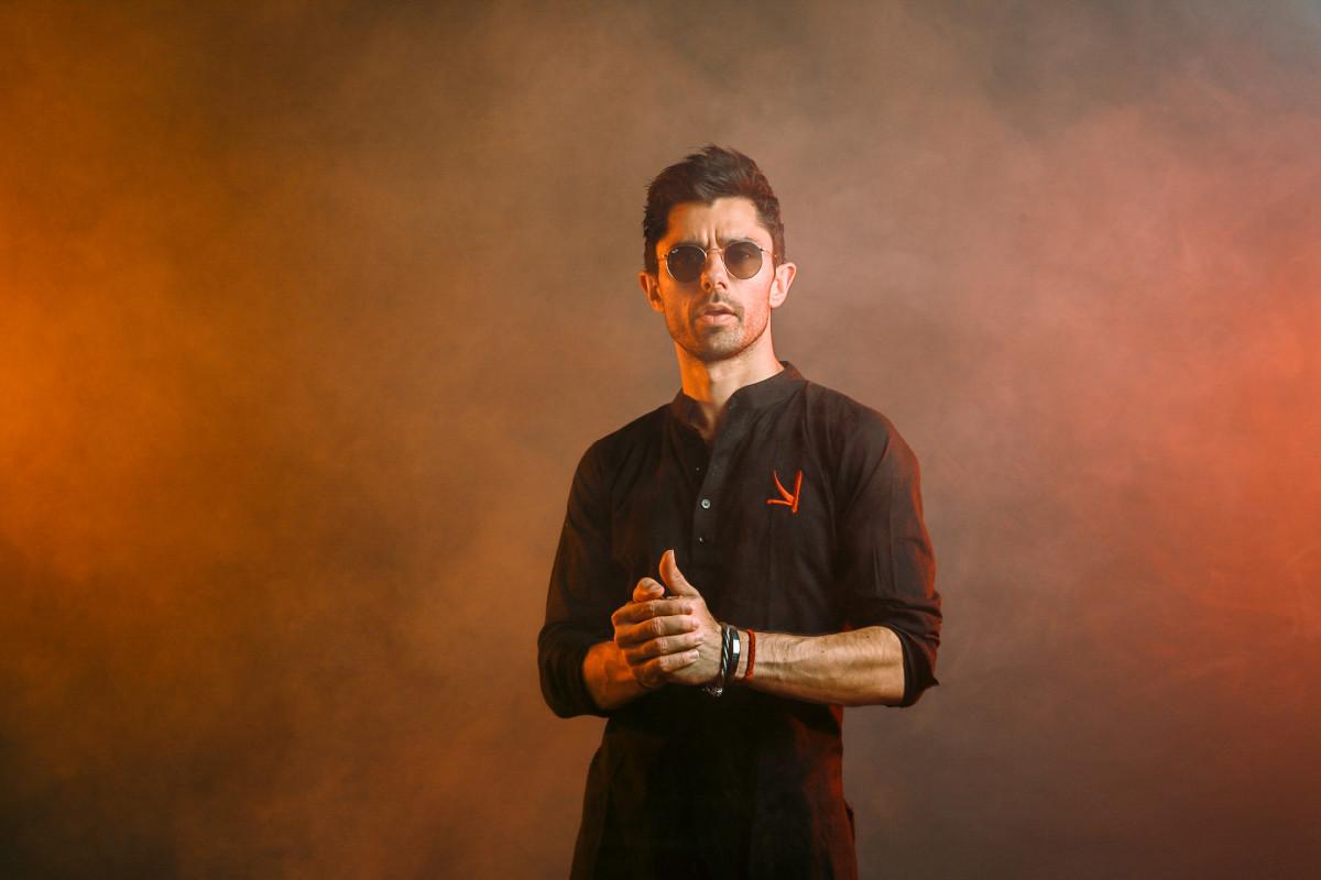 DJ/producer KSHMR over a reddish background.