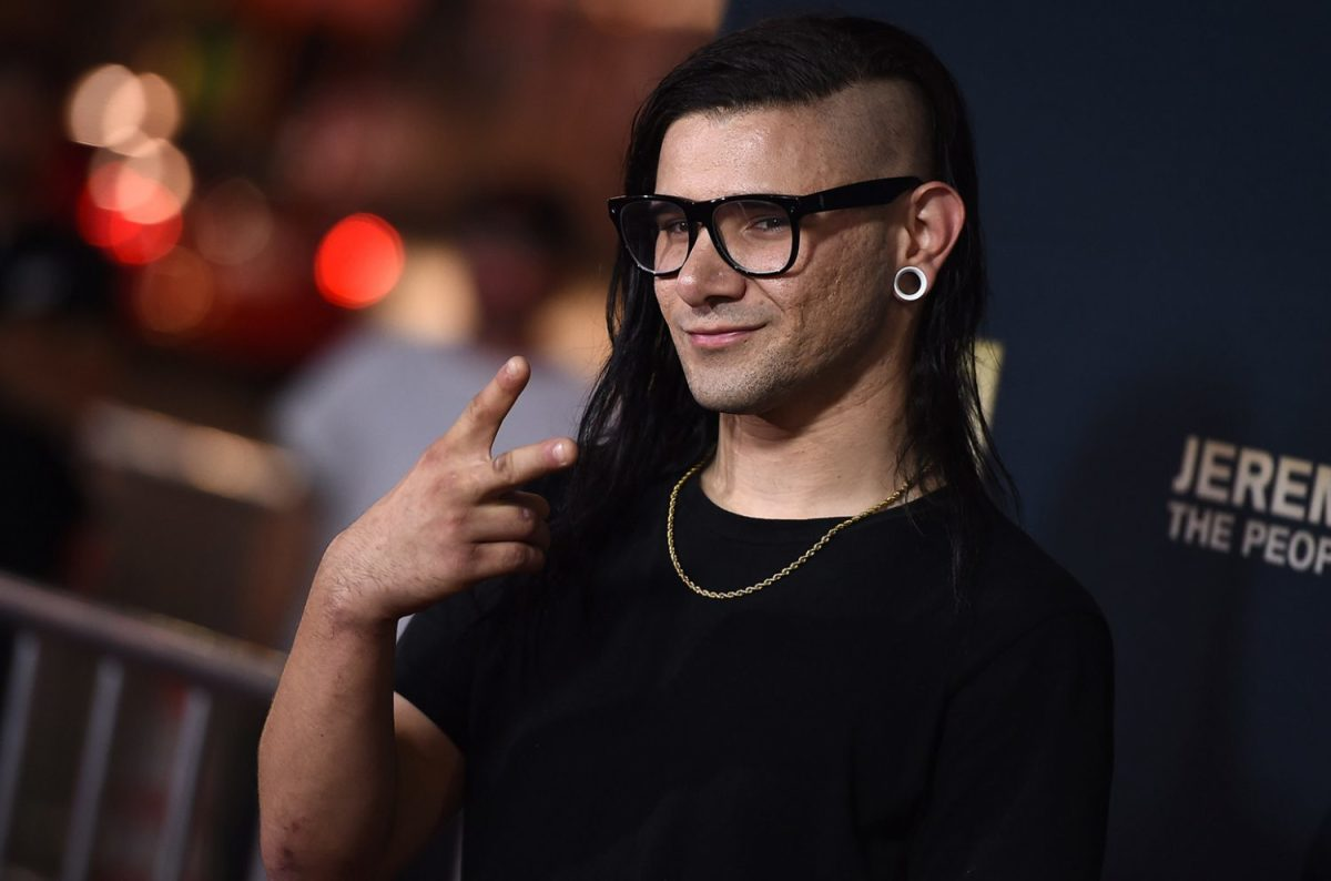 EDM DJ/producer Skrillex flashing a peace sign at a red carpet event.