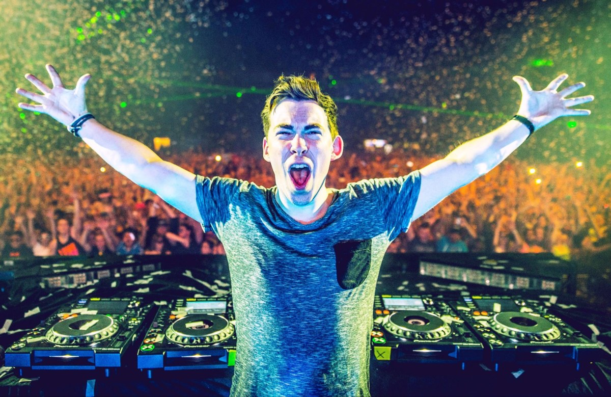 Hardwell with arms stretched out behind the DJ decks during a performance as confetti falls over the crowd in the background.