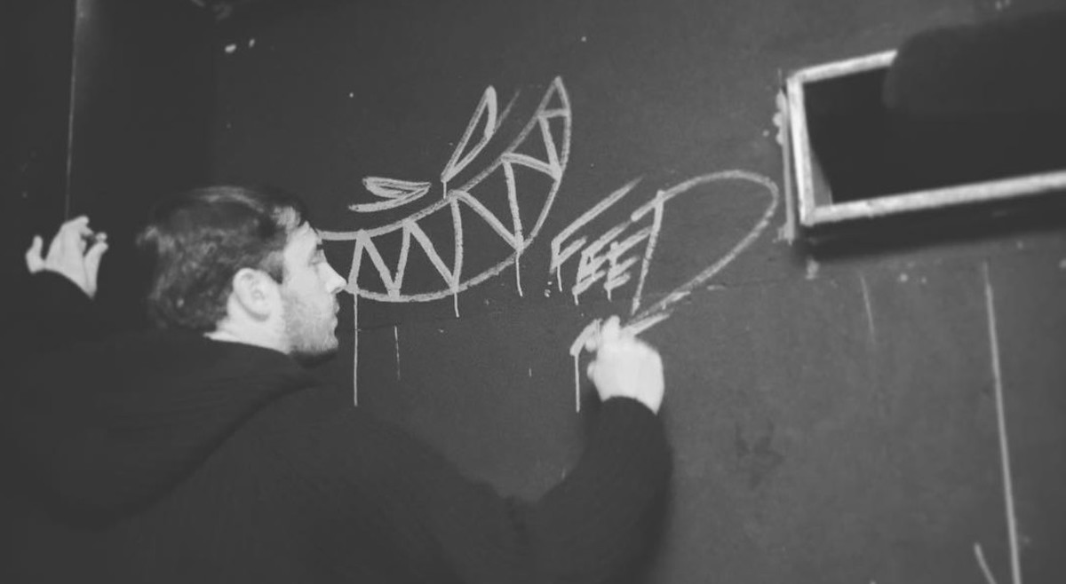 Feed Me A.K.A. Jon Gooch drawing his logo on a wall.