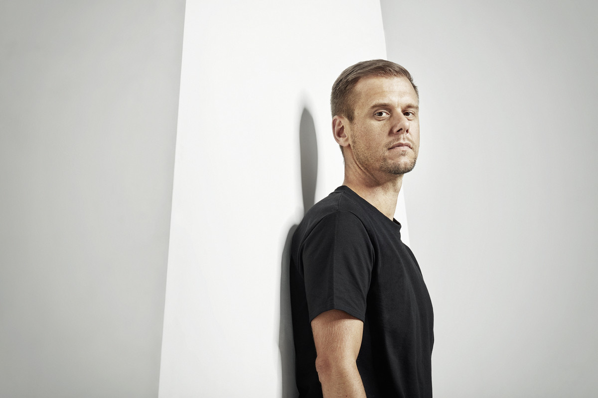 A color press photo of Armin van Buuren wearing a black tee shirt and standing against a giant letter A.