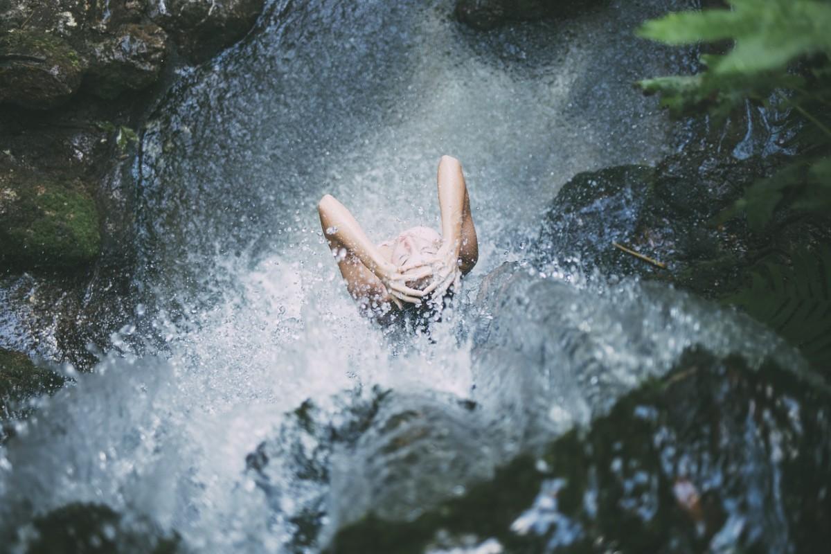 woman washing under waterfall